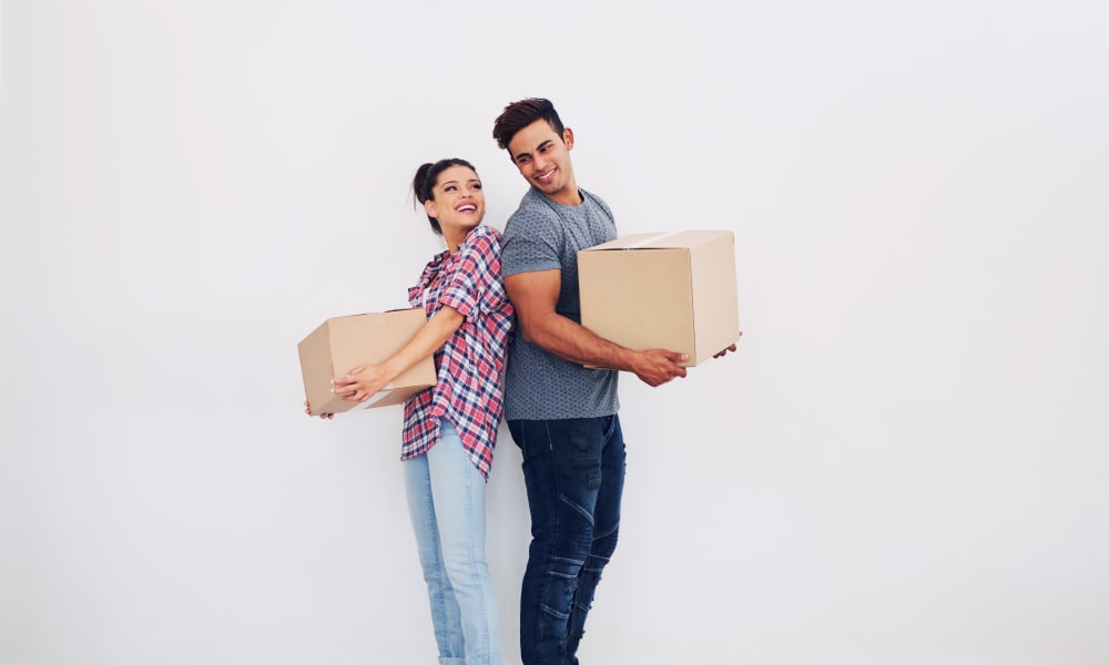 Individuals holding boxes from a recent auction at Devon Self Storage