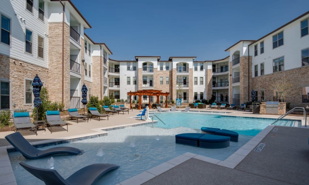 Large resort style swimming pool with lounges in the shallow end at Bellrock Upper North in Haltom City, Texas