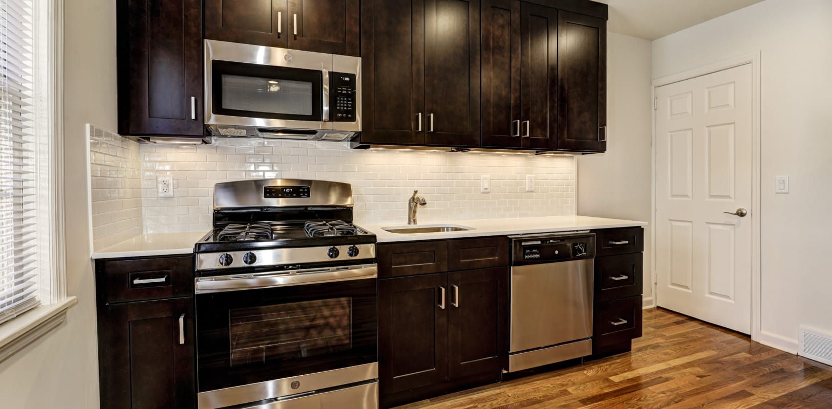 Spacious kitchen with stainless-steel appliances and wood-style flooring at General Wayne Townhomes and Ridgedale Gardens in Madison, New Jersey