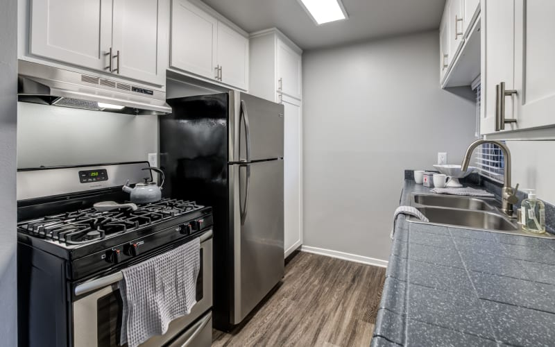 Renovated kitchen with white cabinets and black and stainless steel appliances at Kendallwood Apartments in Whittier, California