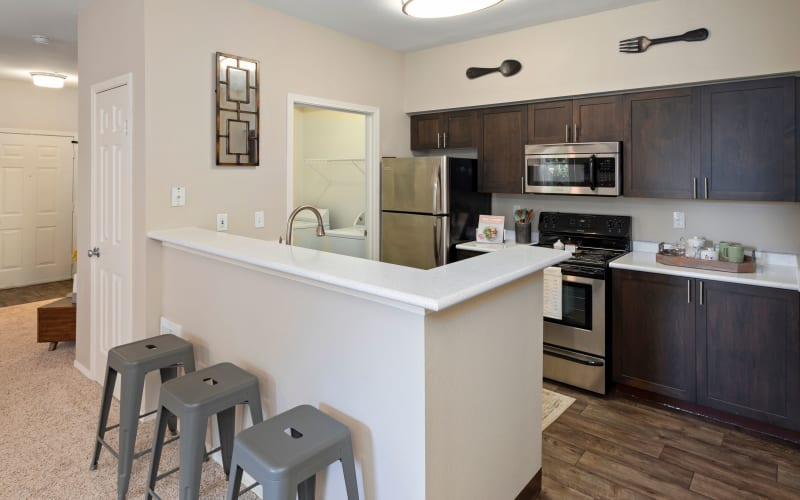 A renovated kitchen with brown cabinets, a bar area and stainless steel appliances at HighGrove Apartments in Everett, Washington