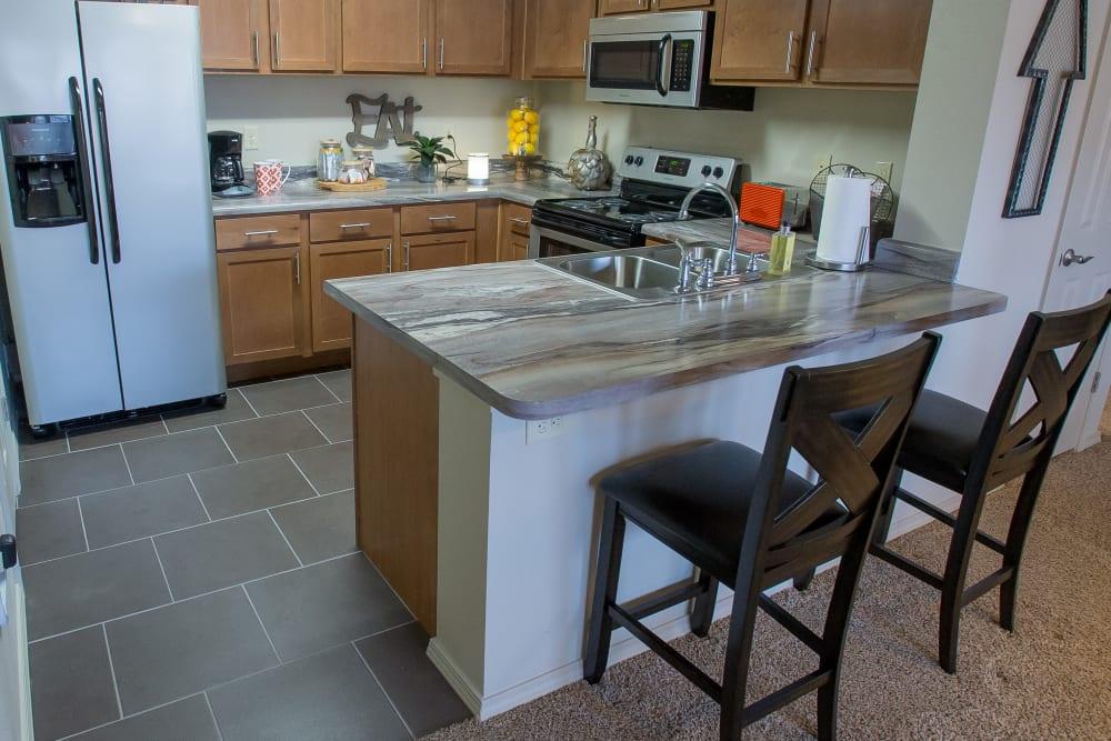 Kitchen with bar style seating at lPortofino Apartmentsin Wichita, Kansas