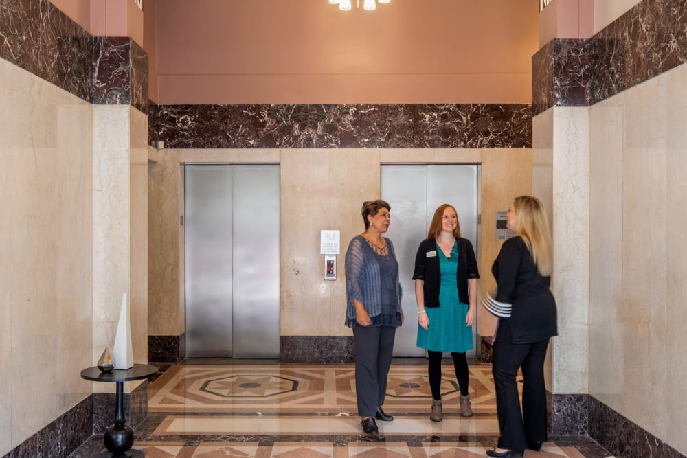 3 people talking by the elevators at Regency Palms Long Beach in Long Beach, California