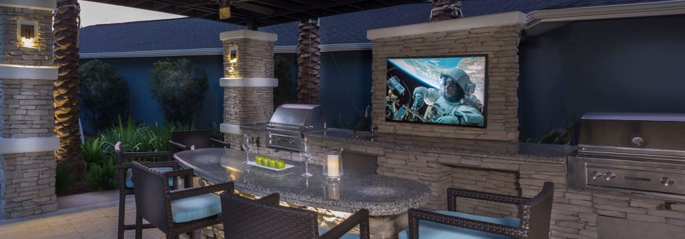 An outdoor lounge with bar seating and a flat-screen TV at Greenhouse in Houston, Texas