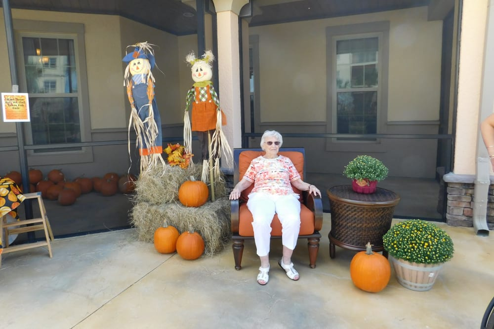 resident taking a photo with pumpkins at Merrill Gardens at Solivita Marketplace in Kissimmee, Florida.