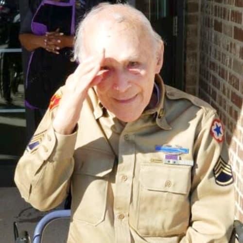 Smiling veteran giving a salute at Oxford Glen Memory Care at Carrollton in Carrollton, Texas
