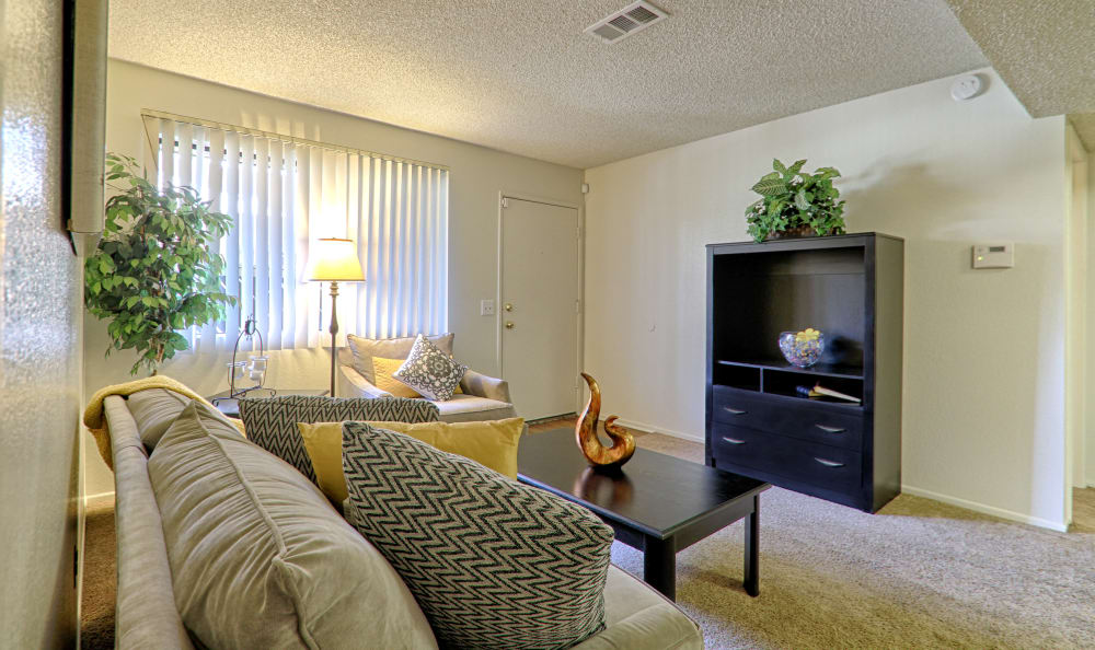 Wide view of spacious living room with plenty of natural light in model home at Creekside Village Apartment Homes in San Bernardino, CA