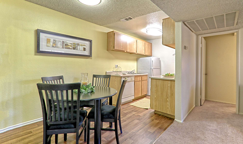 View of the dining area with kitchen in background in model home at Creekside Village Apartment Homes in San Bernardino, CA