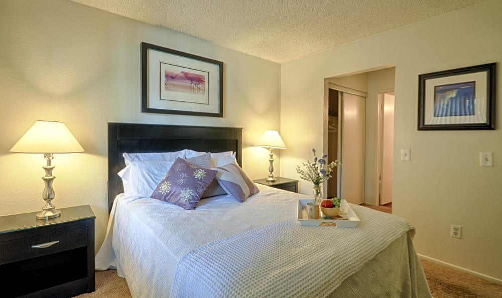 Large, well-lit bedroom in model apartment home at Creekside Village Apartment Homes in San Bernardino, CA