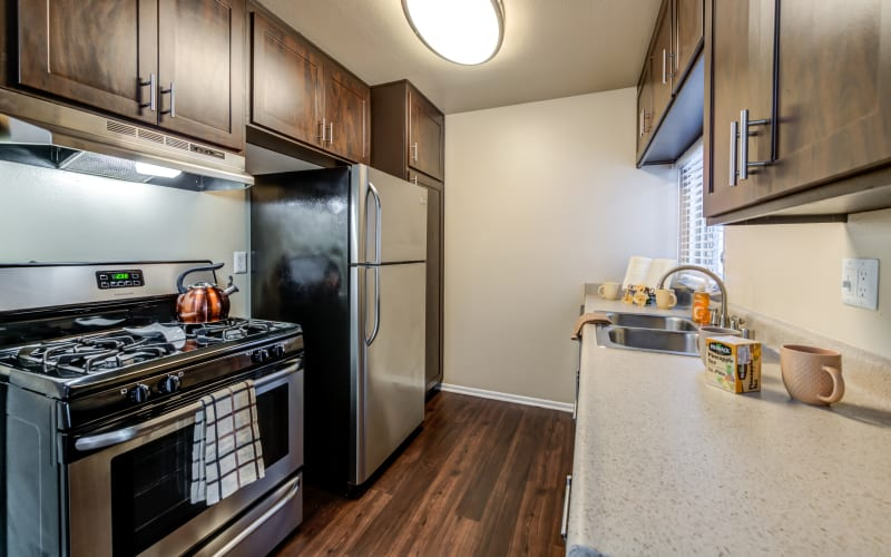 Renovated kitchen with stainless steel appliances and brown cabinets at Kendallwood Apartments in Whittier, California