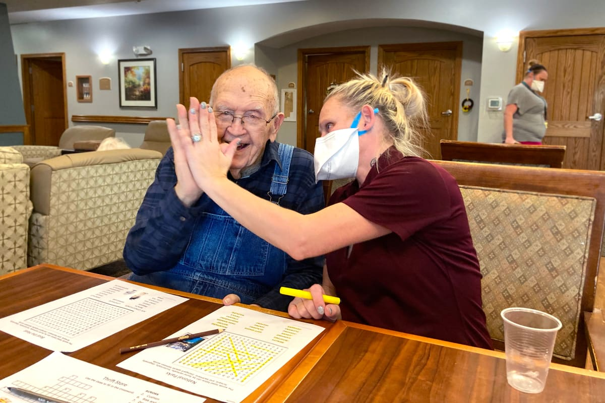 Masked team member high fiving a resident at Glen Carr House Memory Care in Derby, Kansas
