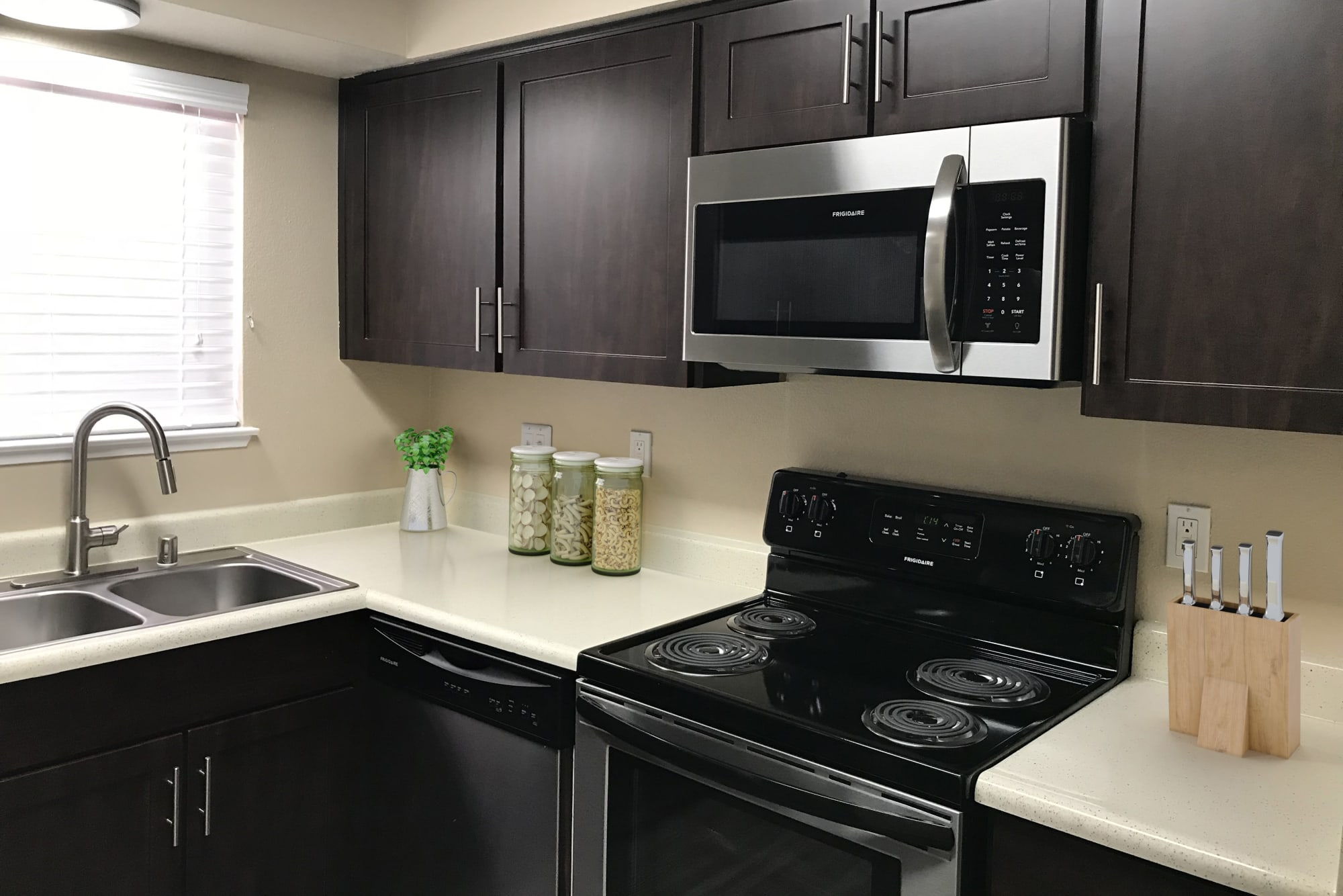 Renovated kitchen with brown cabinets and stainless steel appliances at Bennington Apartments in Fairfield, California