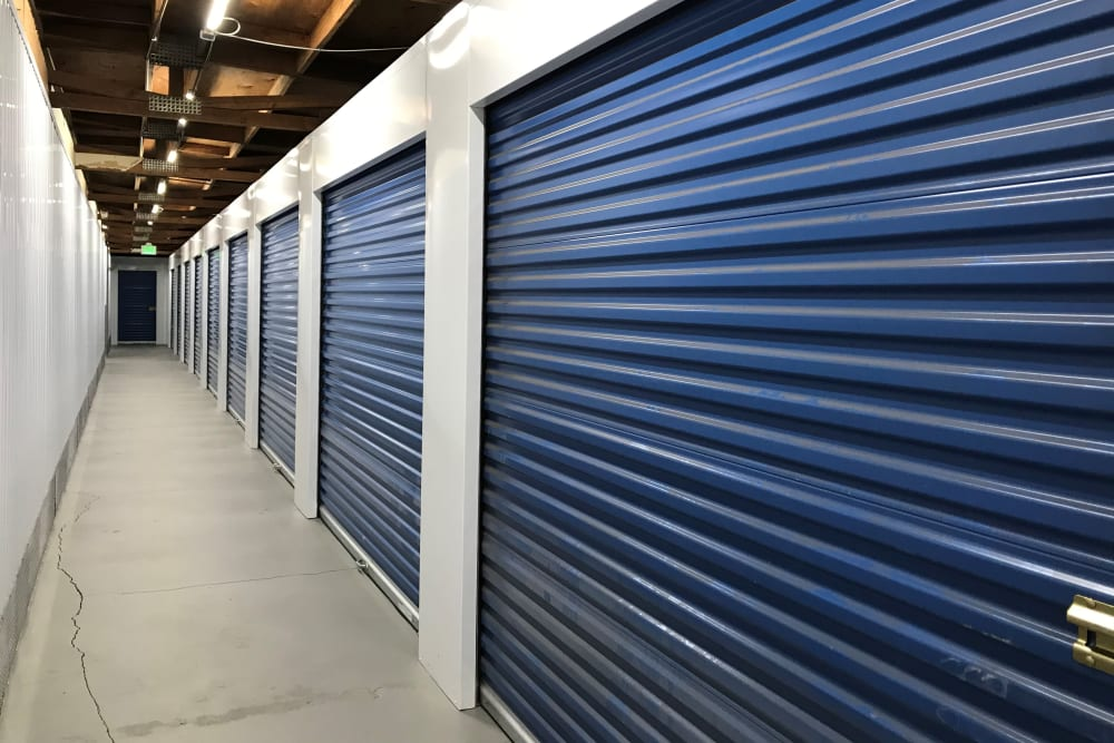 Indoor hallway access to large storage units at Storage Solutions in Pomona, California