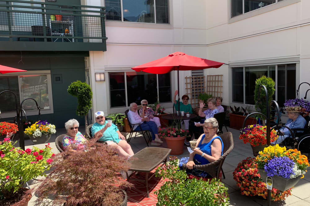 Residents enjoying the weather in the courtyard at Merrill Gardens at Tacoma in Tacoma, Washington.