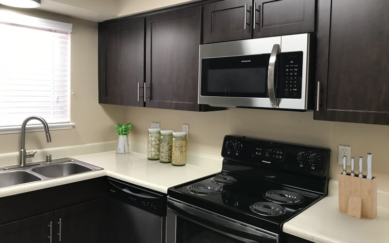 Renovated kitchen with espresso cabinets and stainless steel appliances at Bennington Apartments in Fairfield, California