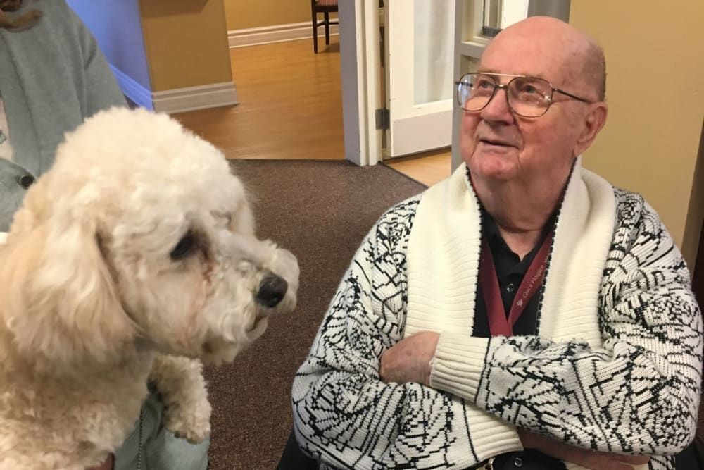 A resident being visited by a friendly dog at The Woods of Caledonia in Racine, Wisconsin
