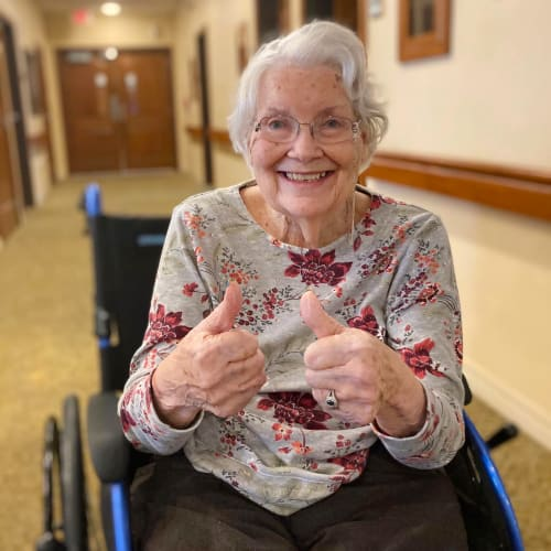 Happy resident giving two thumbs up at Oxford Glen Memory Care at Carrollton in Carrollton, Texas