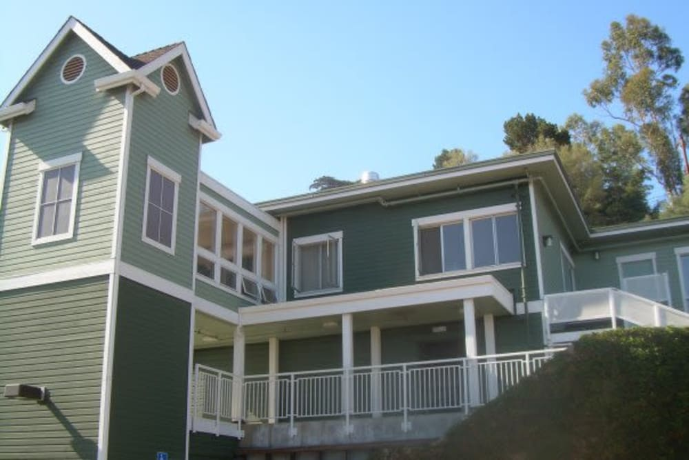 The main building with green tones of paint and white highlights in Vista Terrace of Belmont in Belmont, California