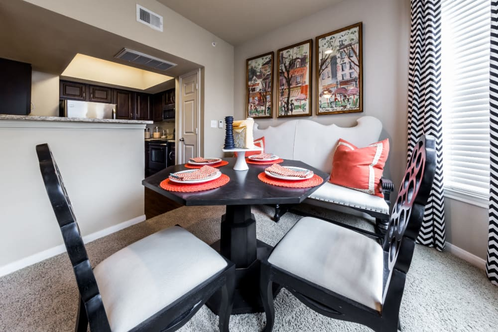 Dining room with large windows overlooking kitchen at Marquis at Stonegate in Fort Worth, Texas