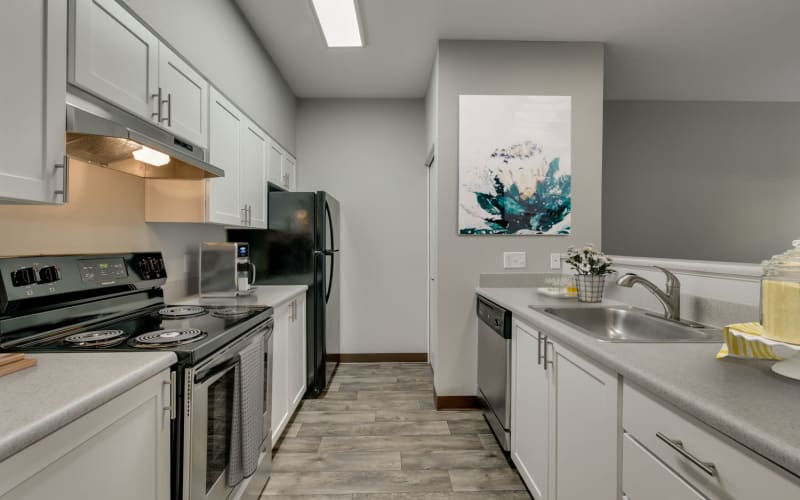 Recently renovated kitchen with white cabinets and stainless steel appliances at The Landings at Morrison Apartments in Gresham, Oregon