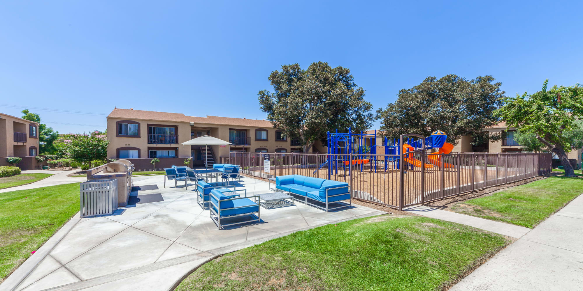 Courtyard with a playground and ample seating at West Fifth Apartments in Ontario, California