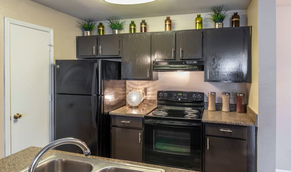 Hardwood floors and contemporary kitchen furnishings at Kenwood Club at the Park in Katy, TX