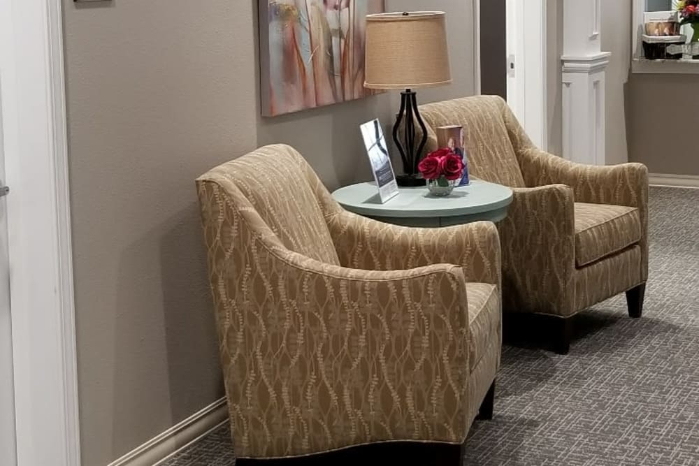Two chairs with a coffee table between them in a hallway at Serenity in East Peoria, Illinois