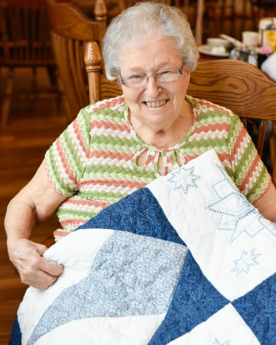Resident showing the quilt she made at Garden Place Red Bud in Red Bud, Illinois.