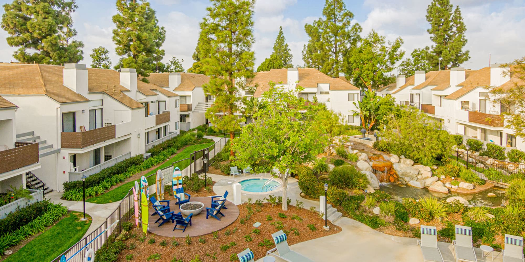 Low aerial view of the spa and fire pit near the swimming pool at Sendero Huntington Beach in Huntington Beach, California