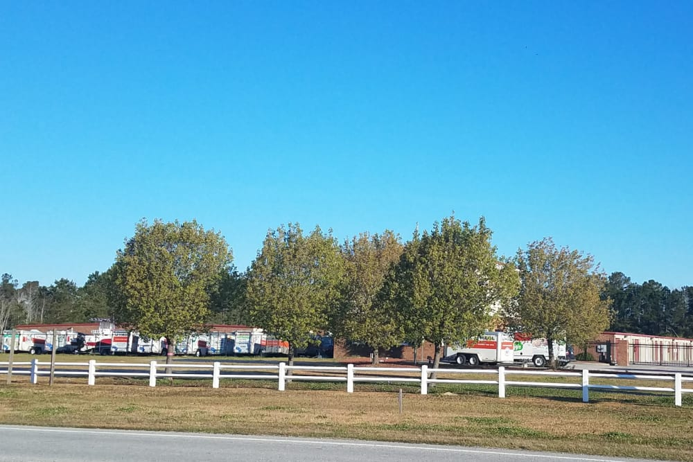 Tree-lined perimeter around storage units at Monster Self Storage in Ocean Isle Beach, North Carolina