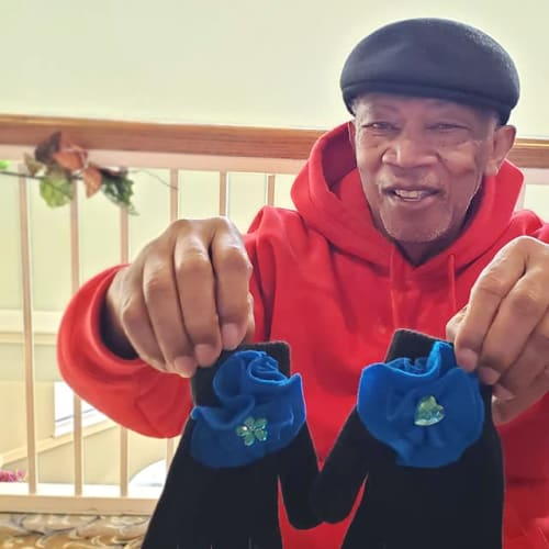 A resident holding up a pair of gloves at Canoe Brook Assisted Living & Memory Care in Catoosa, Oklahoma