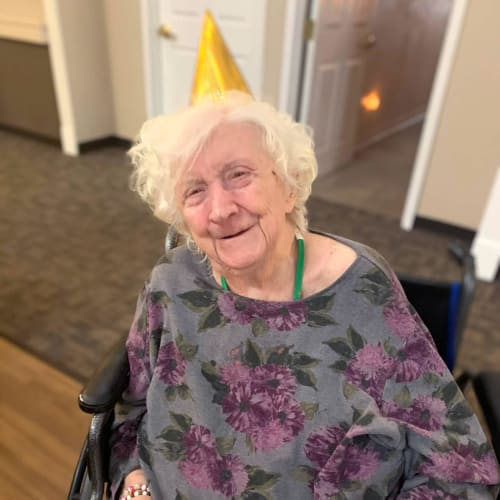 Resident wearing a party hat while holding a cheese and meat spread at Canoe Brook Assisted Living in Broken Arrow, Oklahoma
