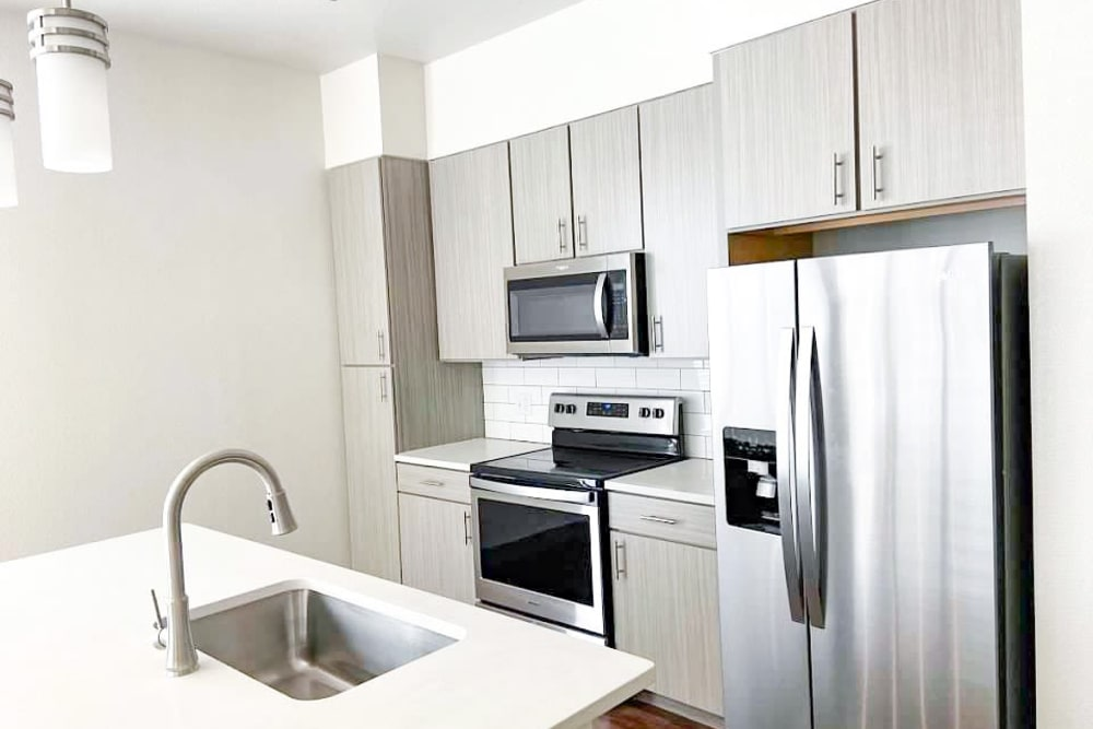 Spacious kitchen with sink in island stainless steel appliances and modern cabinets at The Alcott in Denver, Colorado