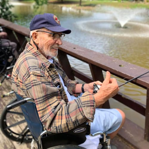 A Resident in a wheelchair sitting outside by a body of water at Oxford Glen Memory Care at Owasso in Owasso, Oklahoma