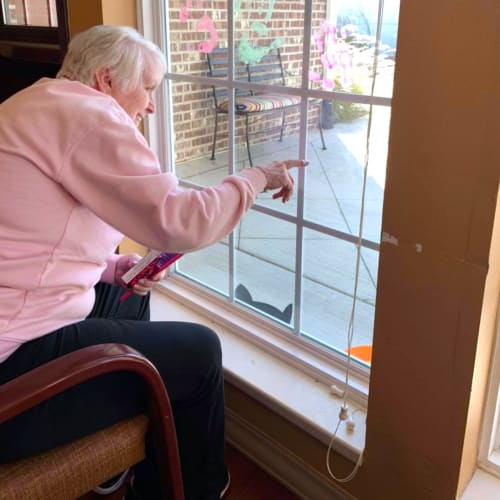 Resident sitting in a chair looking out a window at Oxford Glen Memory Care at Owasso in Owasso, Oklahoma