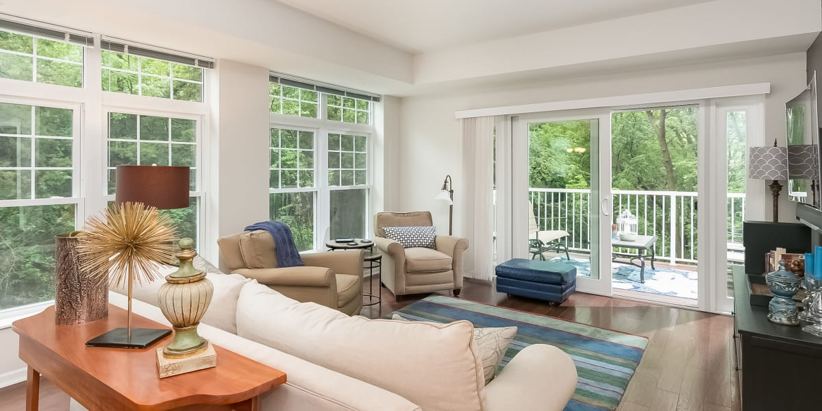 Spacious living room with scenic views and balcony access at Applewood Pointe of Eden Prairie in Eden Prairie, Minnesota