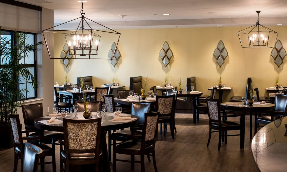 Large dining room with set tables at Keystone Place at Naples Preserve in Naples, Florida