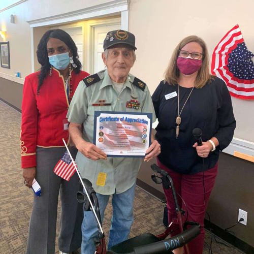 Veteran resident receiving a certificate of appreciation at Canoe Brook Assisted Living in Broken Arrow, Oklahoma