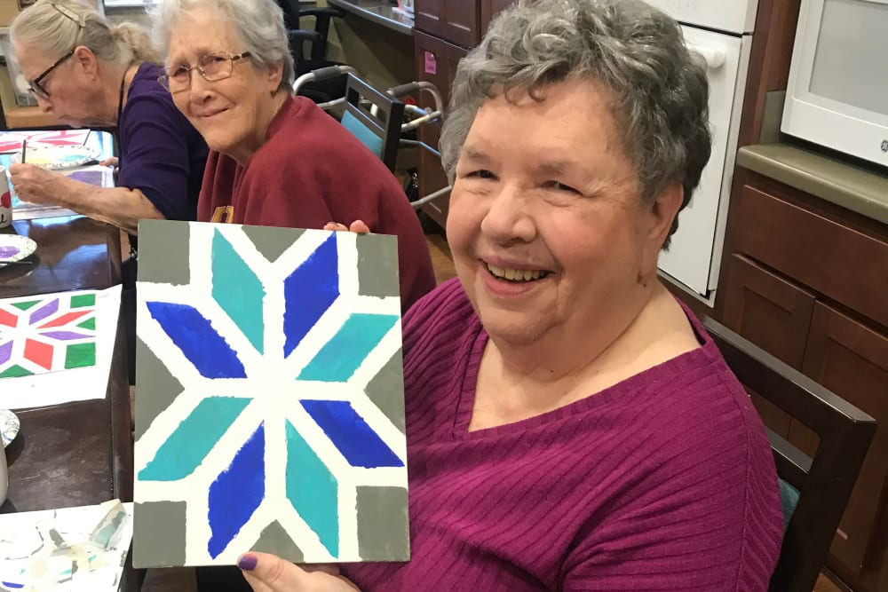 Resident showing her artwork at Edencrest at Riverwoods in Des Moines, Iowa