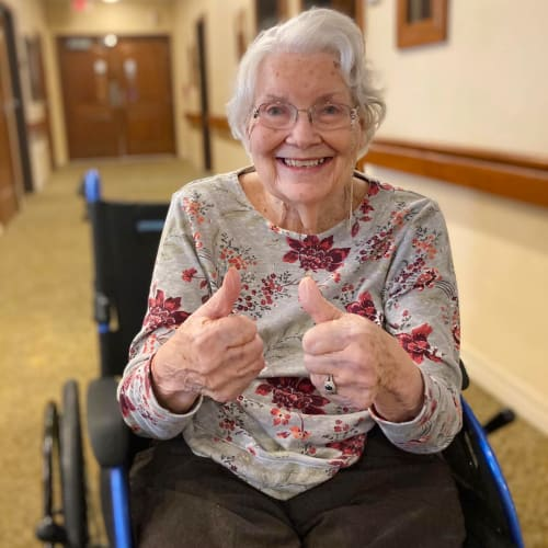Resident sitting in a wheelchair giving 2 'thumbs up' at Oxford Glen Memory Care at Carrollton in Carrollton, Texas