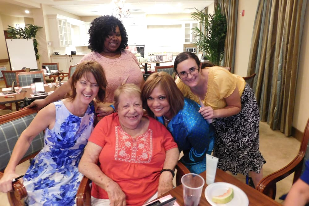 Resident and family members posing for a picture at Merrill Gardens at Solivita Marketplace in Kissimmee, Florida.