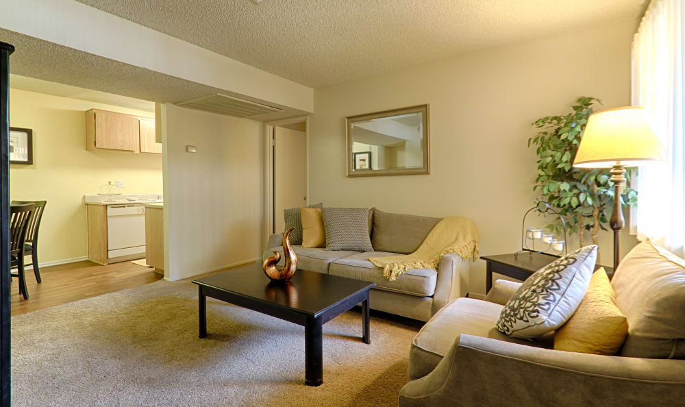Living room view with kitchen in the background in model home at Creekside Village Apartment Homes in San Bernardino, CA
