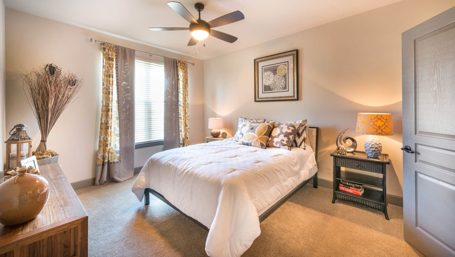 Draped windows in the well-furnished master bedroom of a model home at Union At Carrollton Square in Carrollton, Texas
