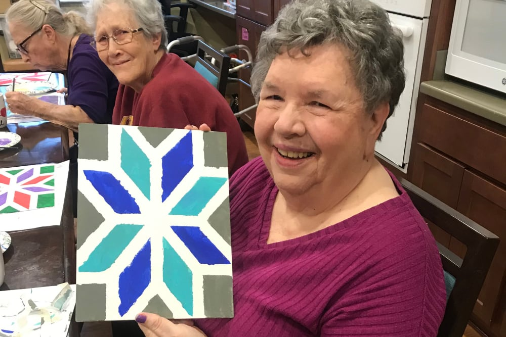 Resident smiling and showing her artwork at Edencrest at Riverwoods in Des Moines, Iowa