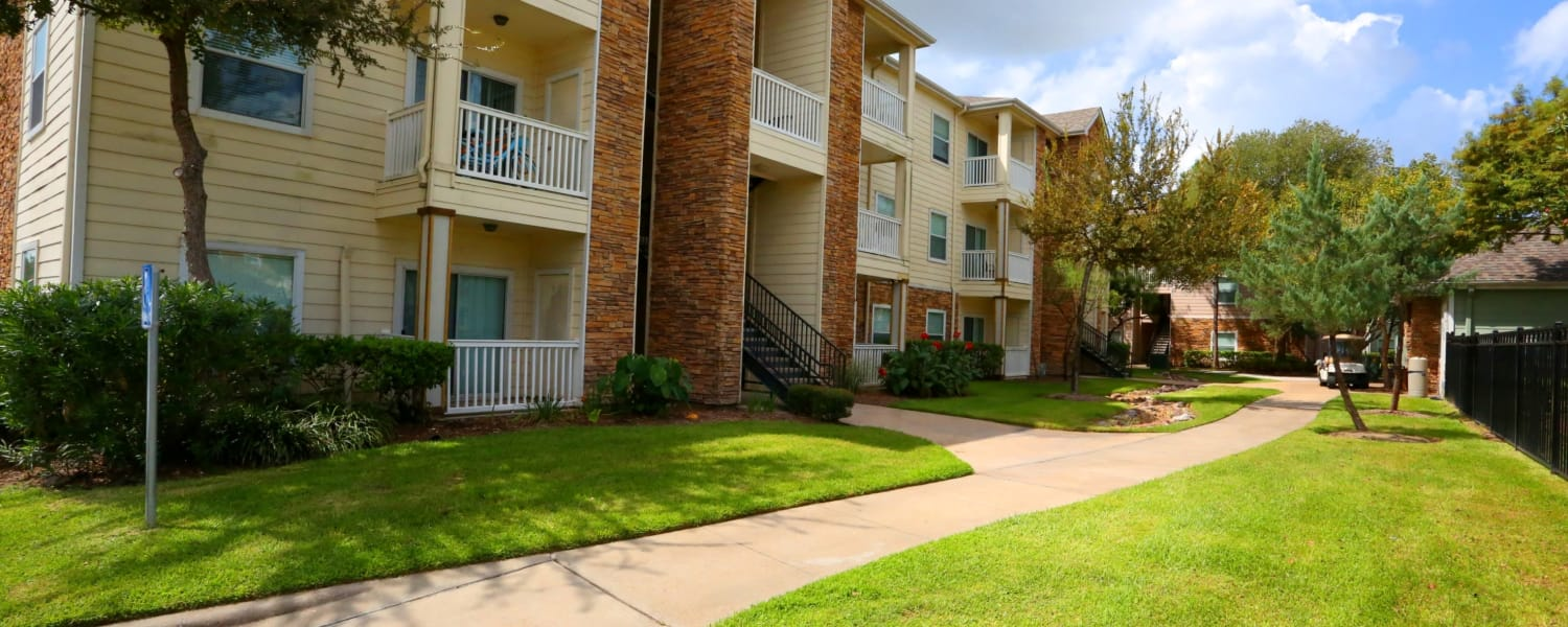 Exterior view of Cornerstone Ranch Apartments in Katy, Texas with lawn and concrete walkways