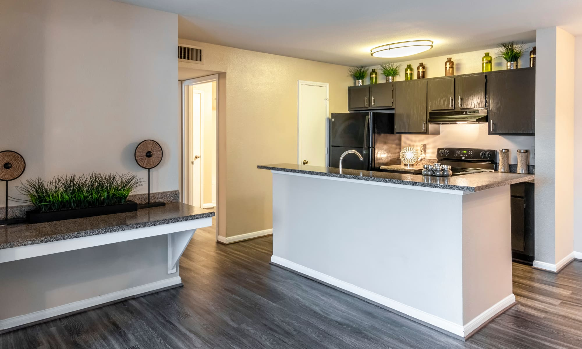 Beautiful hardwood flooring and modern kitchen at Kenwood Club at the Park in Katy, TX