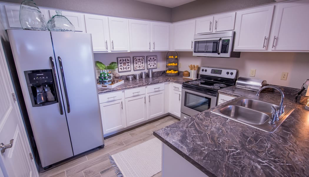 Modern kitchen with granite counters at Scissortail Crossing Apartments in Broken Arrow, Oklahoma