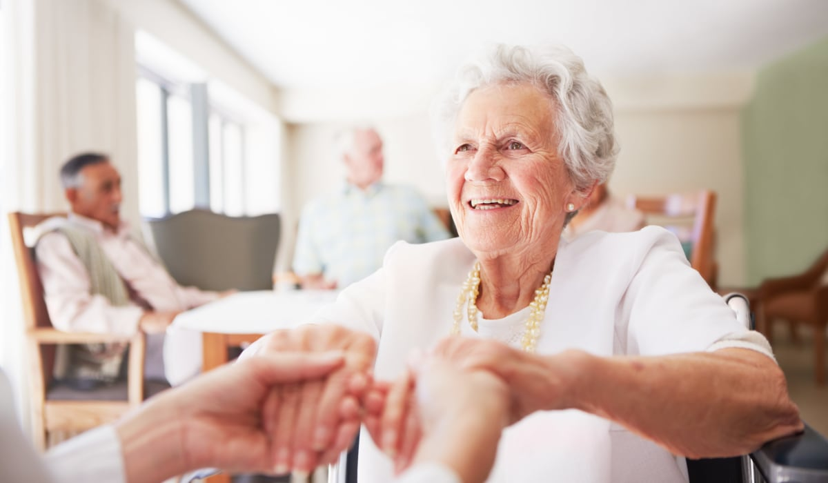 A resident holding hands with a staff member at CERTUS Premier Memory Care Living in Mount Dora, Florida.
