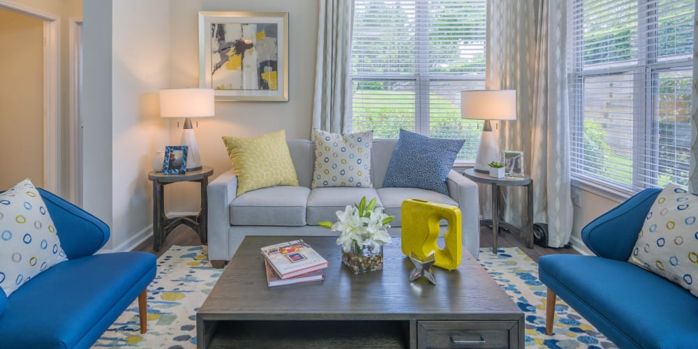 Modern furnishings and large bay windows in a model home's living area at 200 East in Durham, North Carolina