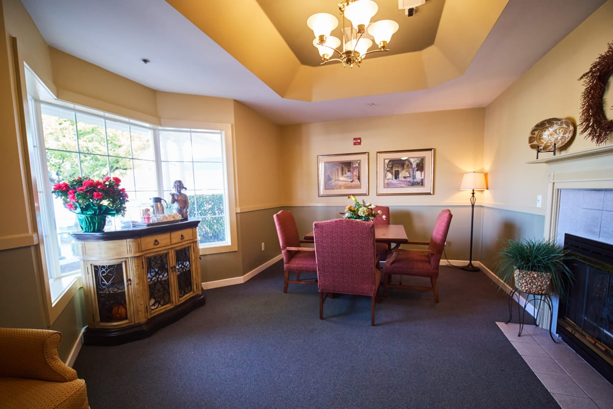 Sunlit activity room with a table and fireplace at Farmington Square Beaverton in Beaverton, Oregon